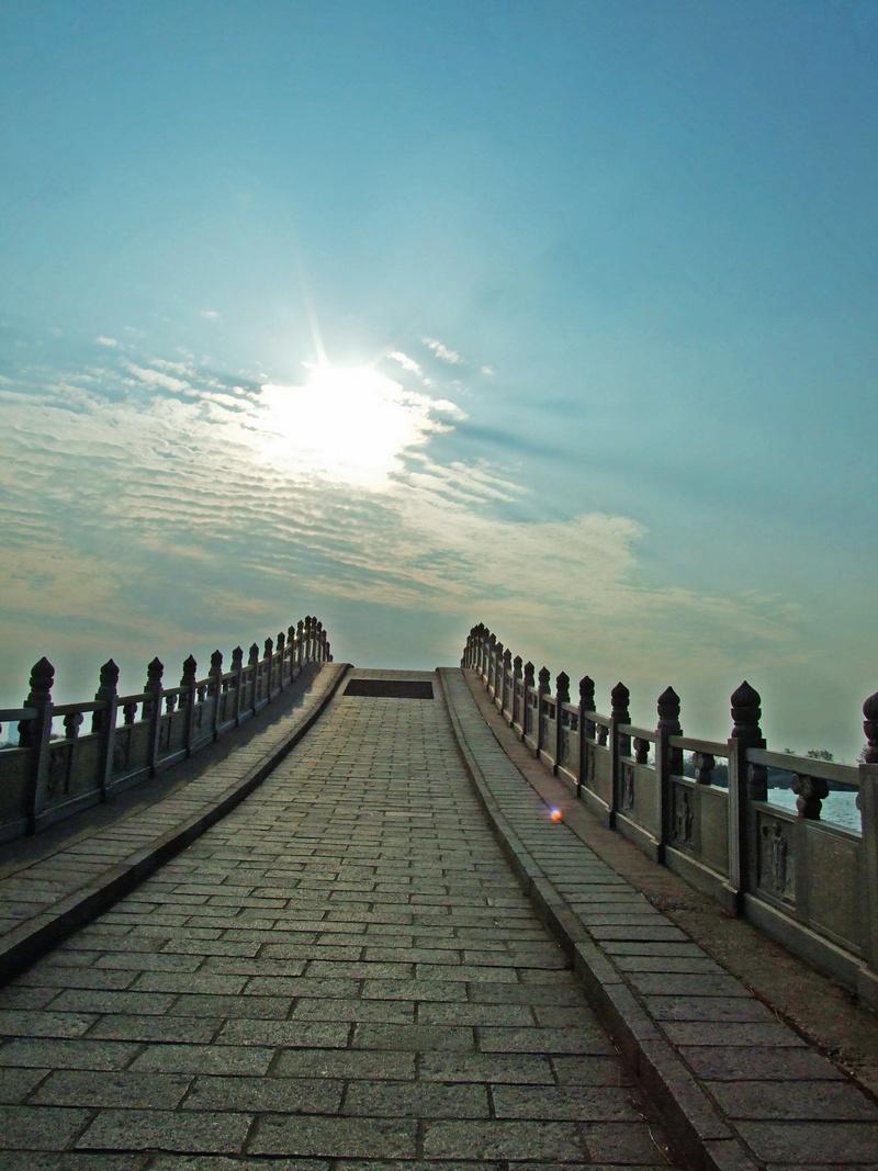 桥上西望,树木葱茏处,是万寿宫 沿湖上长堤西行,翻过高高的拱桥,今天湖上风很大,湖上波浪像海浪一样,拍打着堤岸。桥头两边都是防浪的巨石,大桥显得十分宏伟。站在高高的桥上四面瞭望,天高云淡,波涛滚滚,南面的万寿塔,北面的湖心岛、豫章台,东面的藕香榭,西面的万寿宫尽收眼底。好一派湖上秋光,令人心胸开阔。继续前行,就到达万寿宫门前。南昌万寿宫乃道教圣地的正一派道场,系东晋永嘉六年(公元312年)为奉祀著名道家四相之一、净明道派创始人许逊(字旌阳)而建,当时称旌阳祠,此后曾改称铁柱观、景德观、延真观、妙济万寿宫